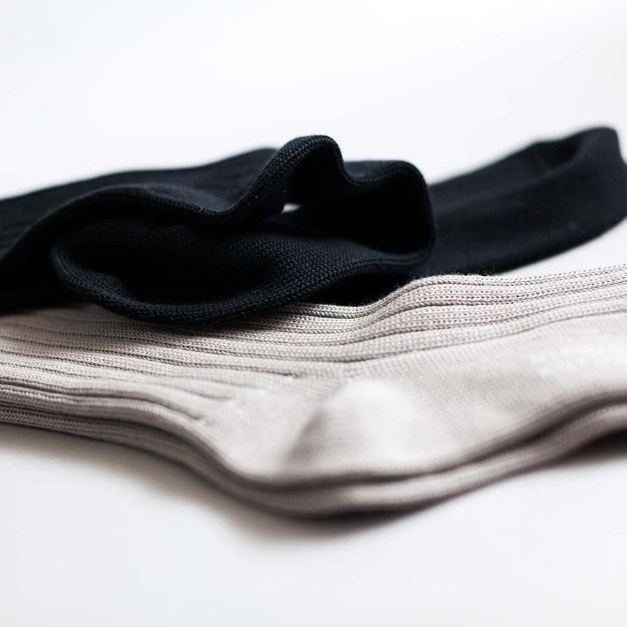 二足の靴下が交差する。ベージュとブラックの二色のコントラスト。リブが美しい。
